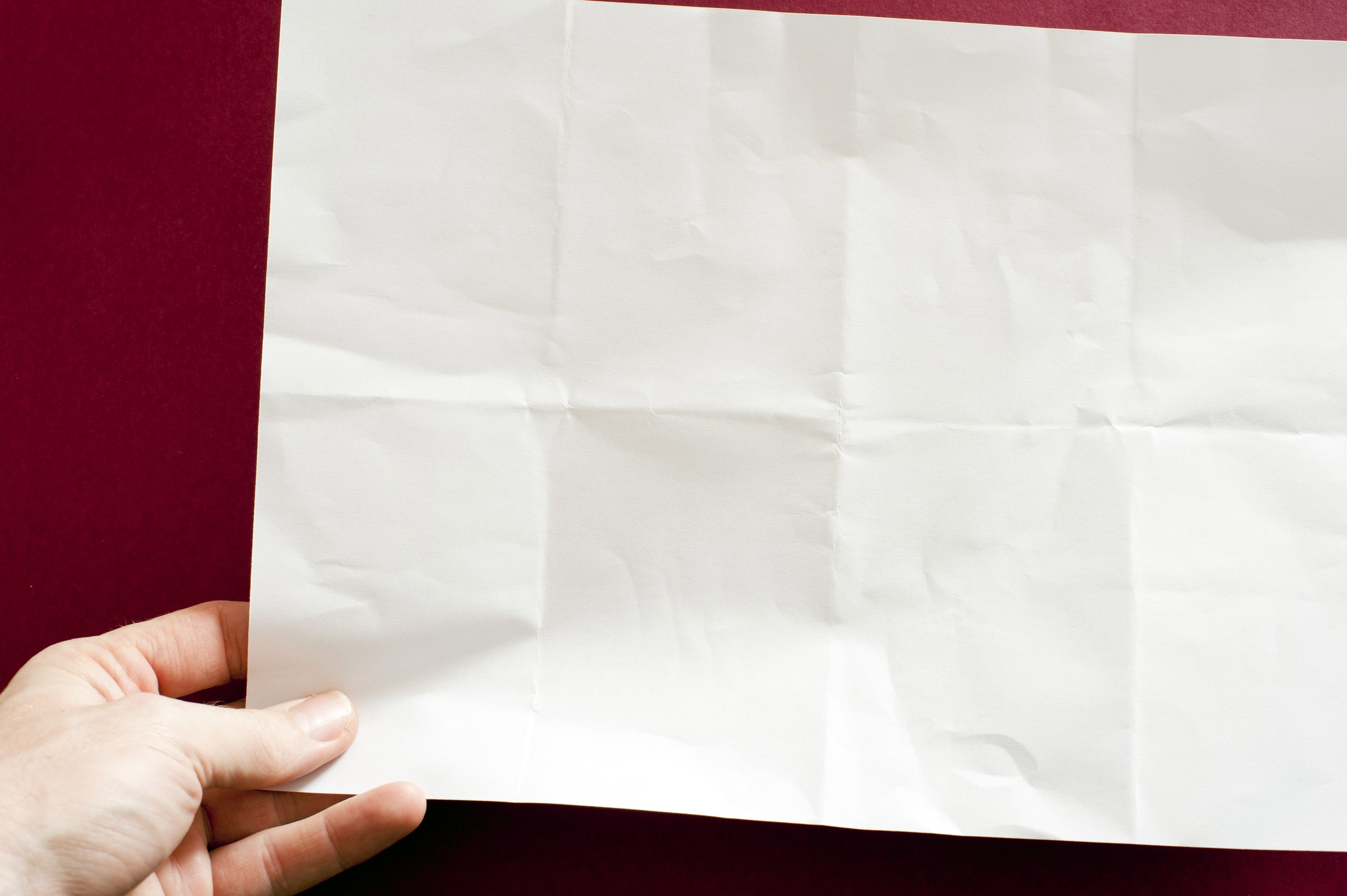 a hand holding a sheet of plain white paper with crease marks