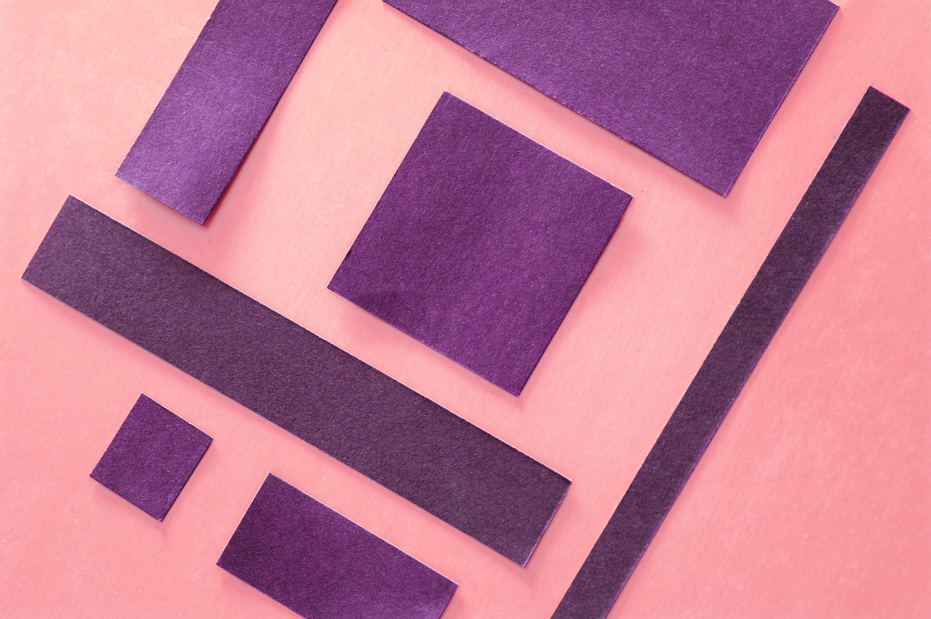 oblique angled squares of paper on a pink background