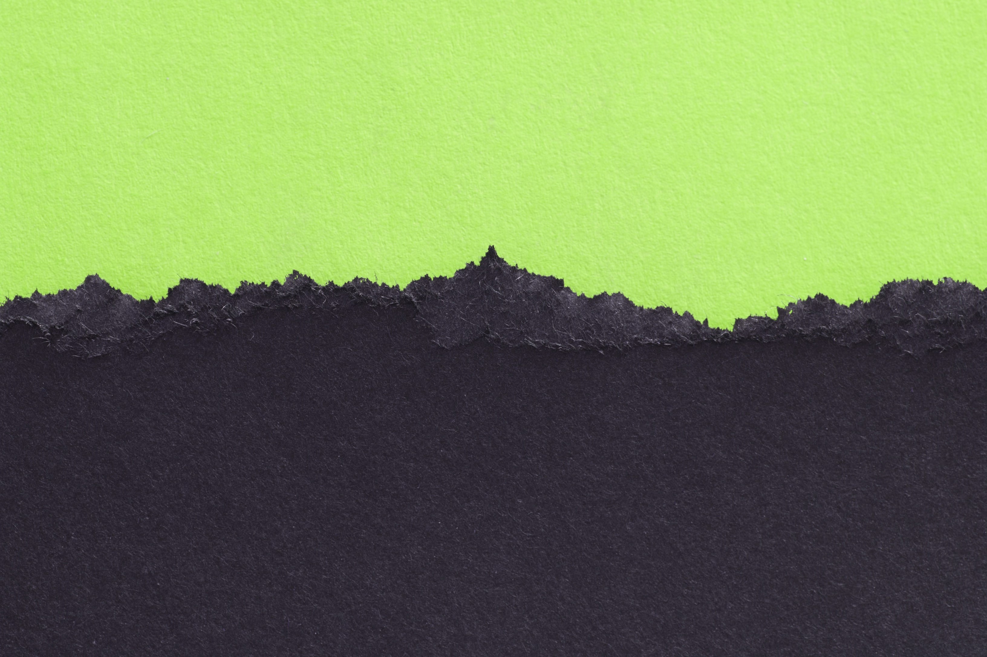 black torn paper and green background