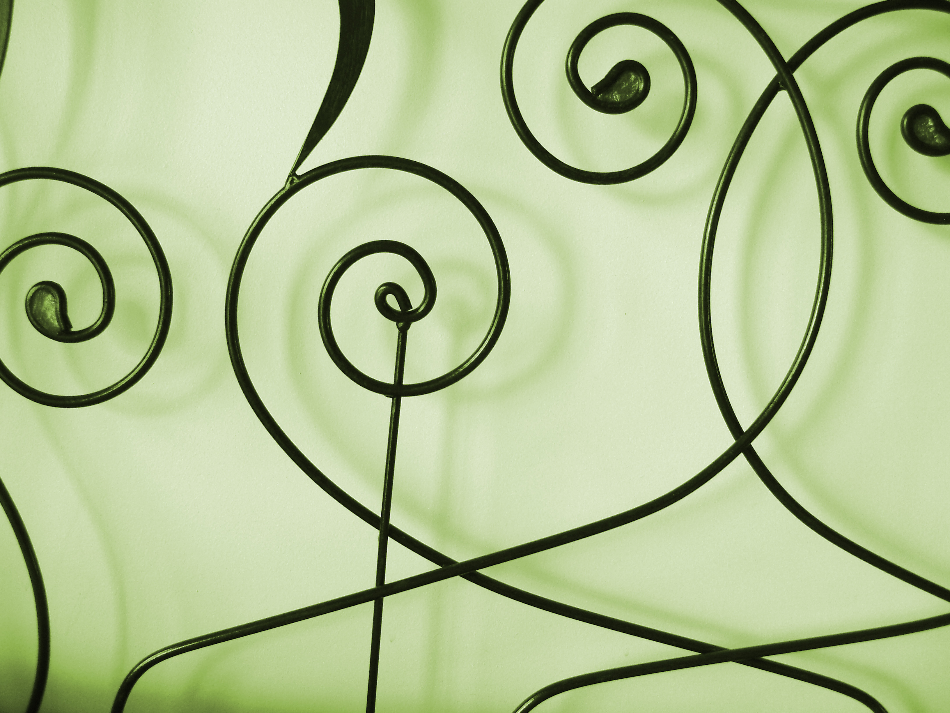 arabesque metal shapes on a green background with shadows