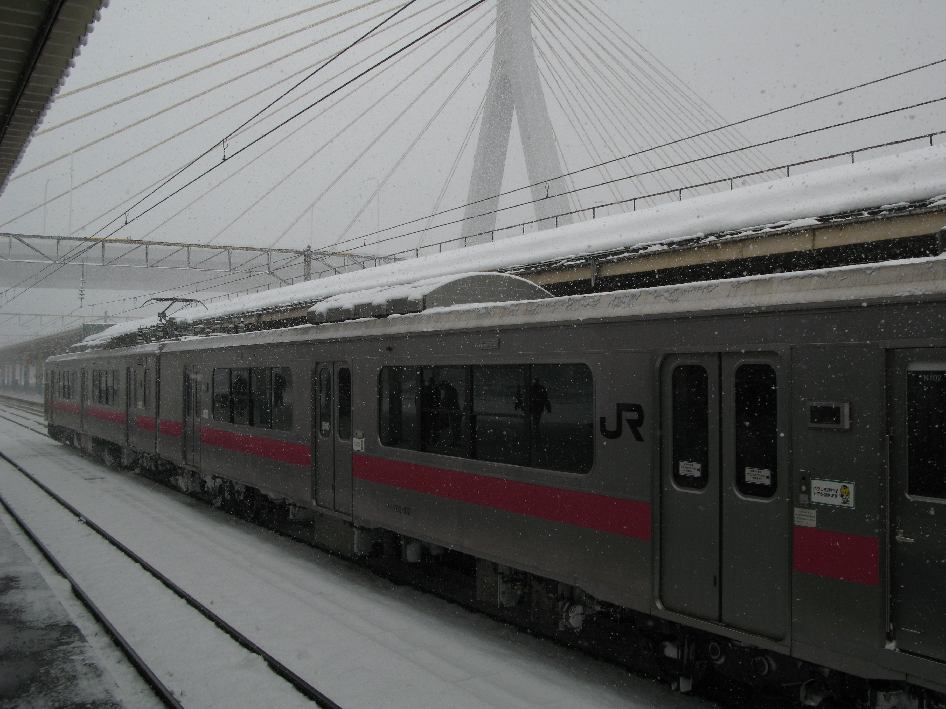 a JR train waiting at a ralway station platform with falling snow