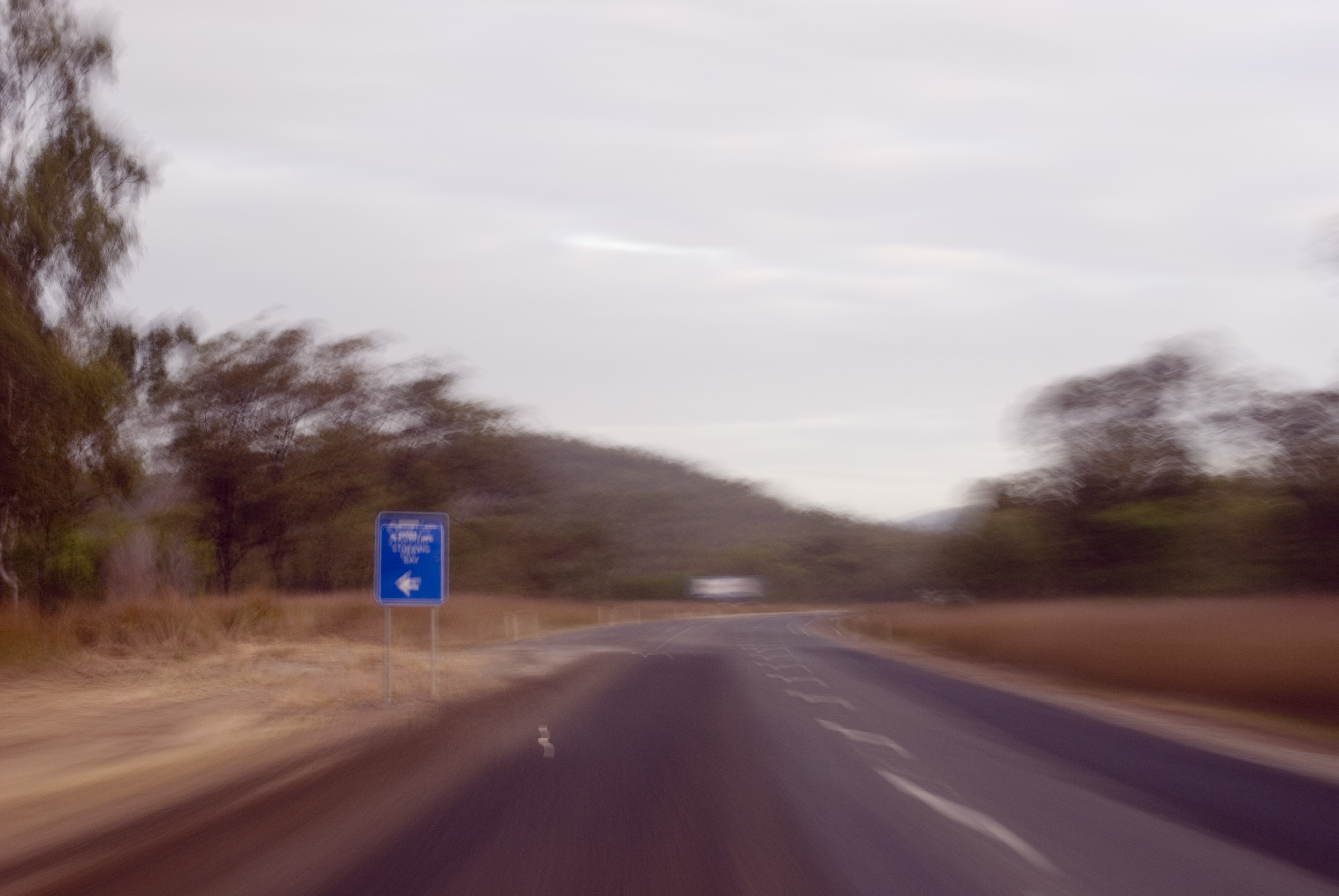 surreal blur on a long drive - blue road sign