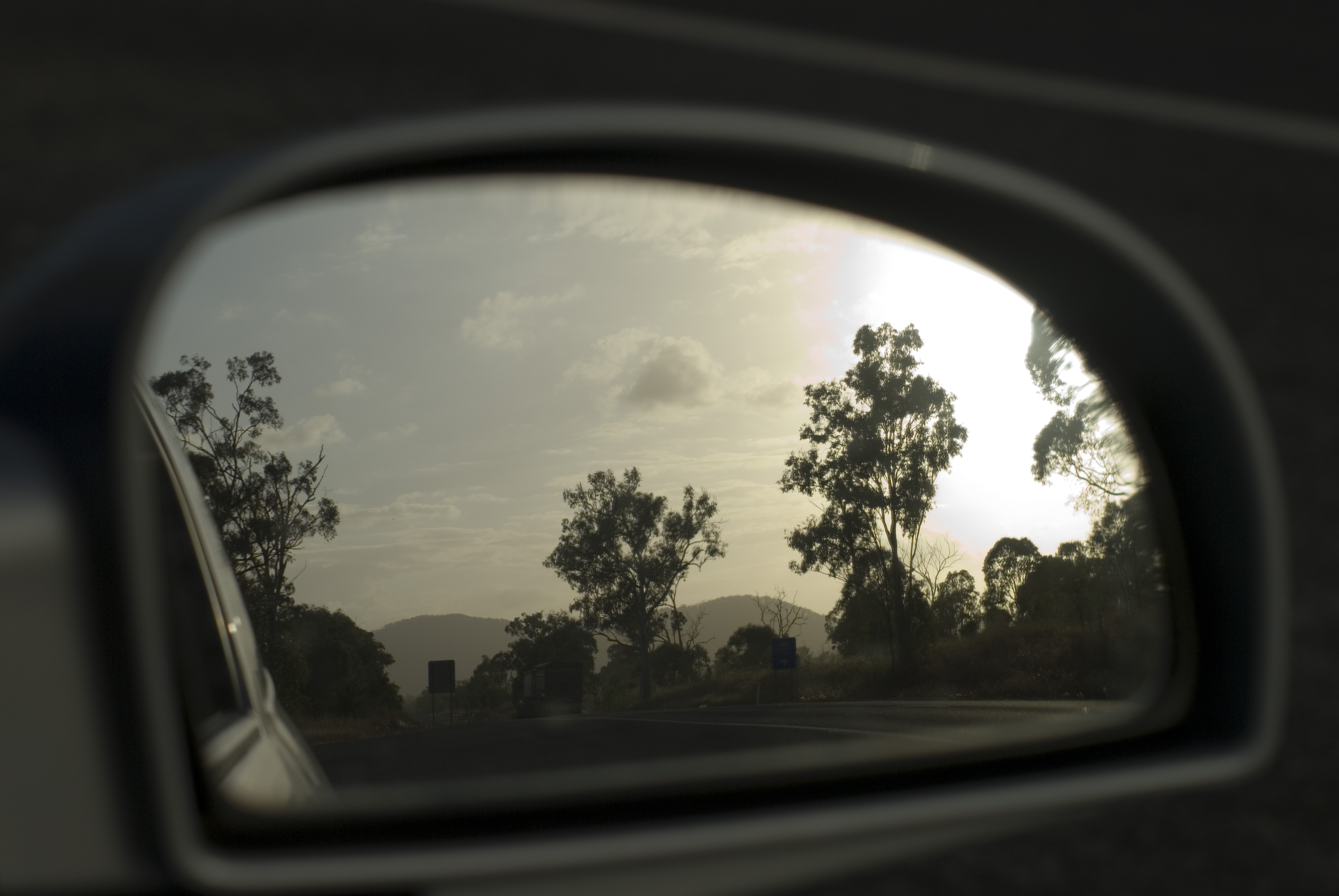 a car side mirror looking back in the evening sun