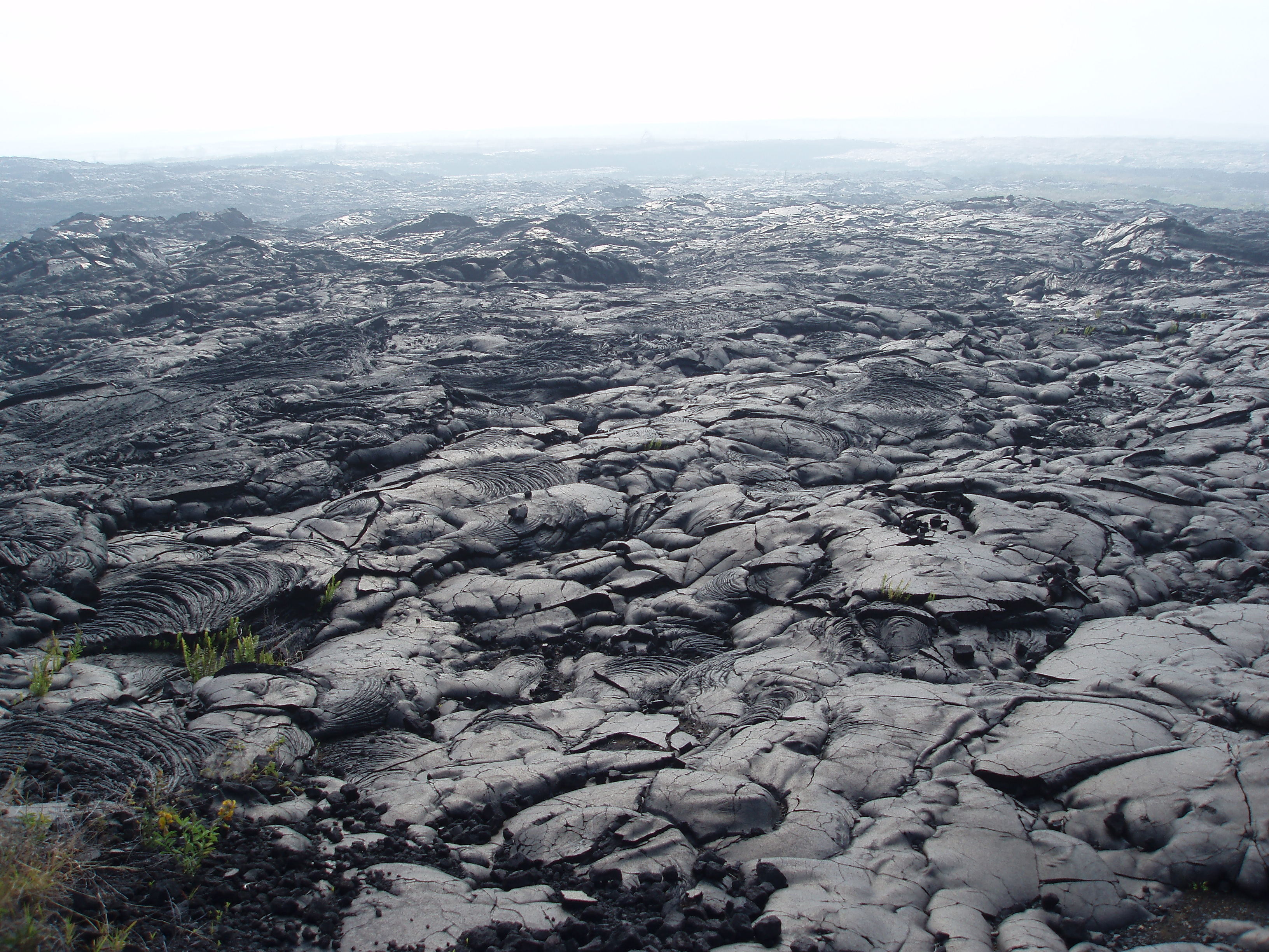 broken surface of a solidified lava field with volcanic gasses in the background