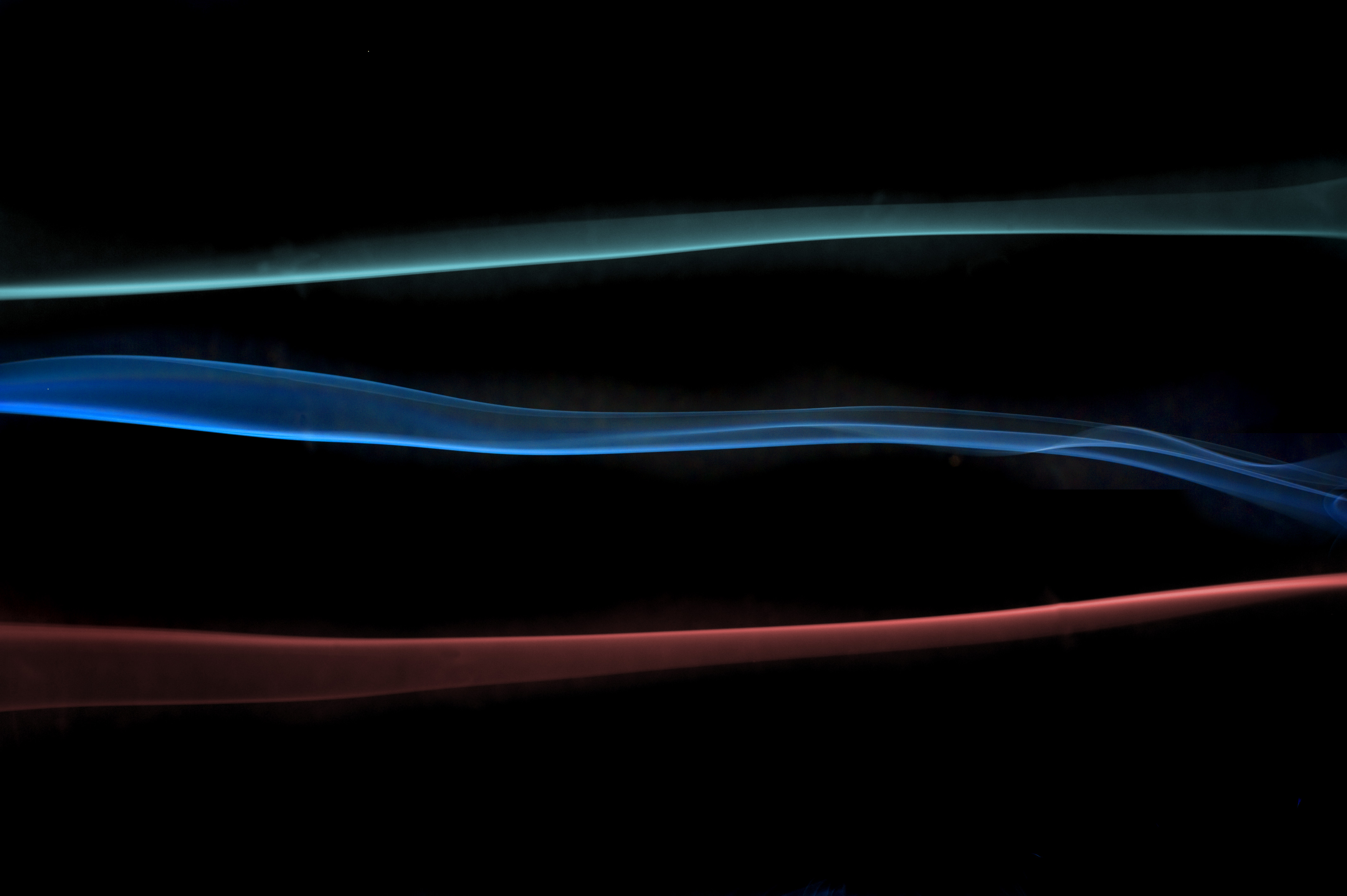organically curving line of smoke in red green and blue primary colours
