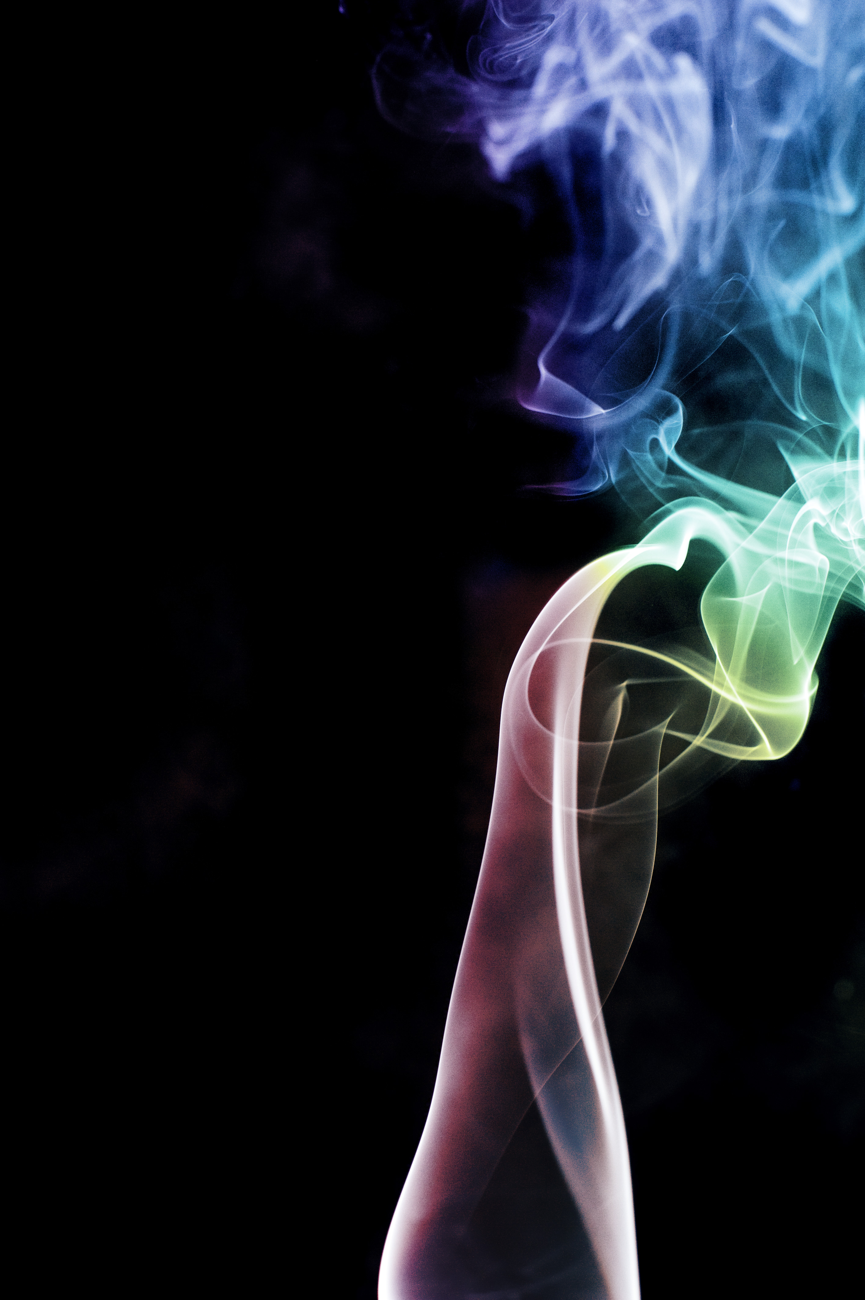 a rainbow of colourful smoke on a black backdrop
