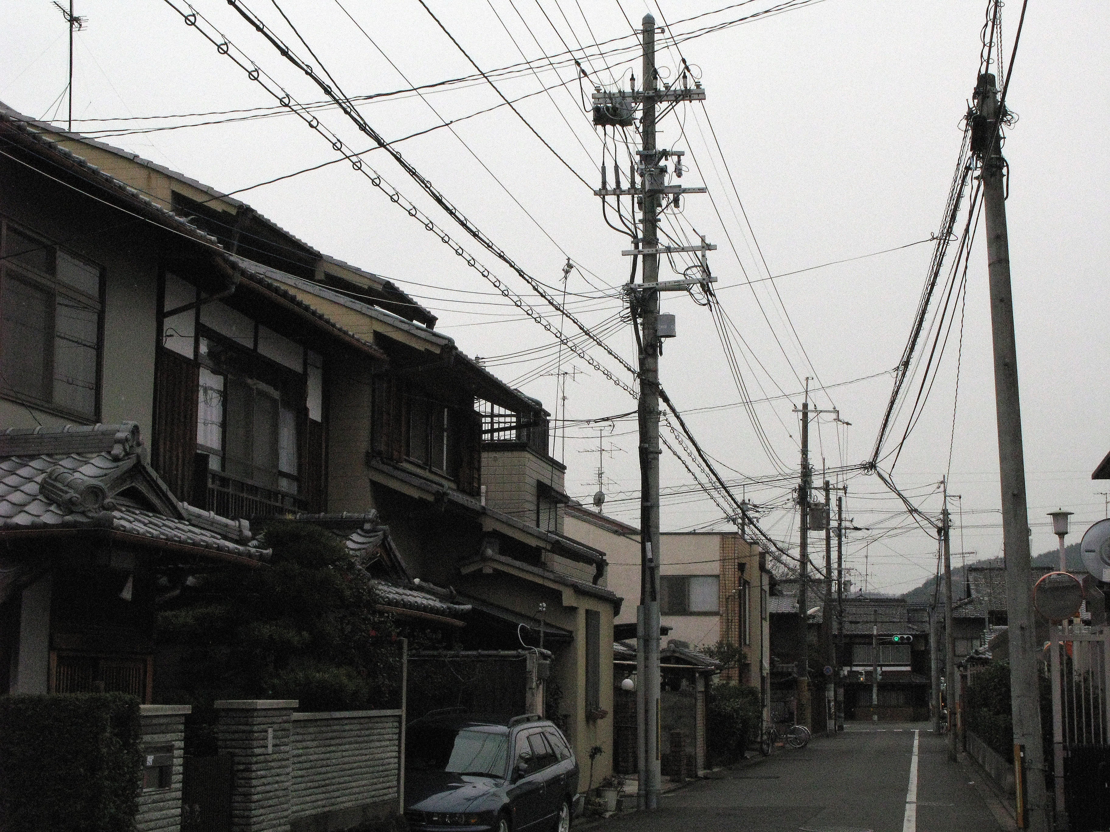 grainy image of power cables strung across a street in japan