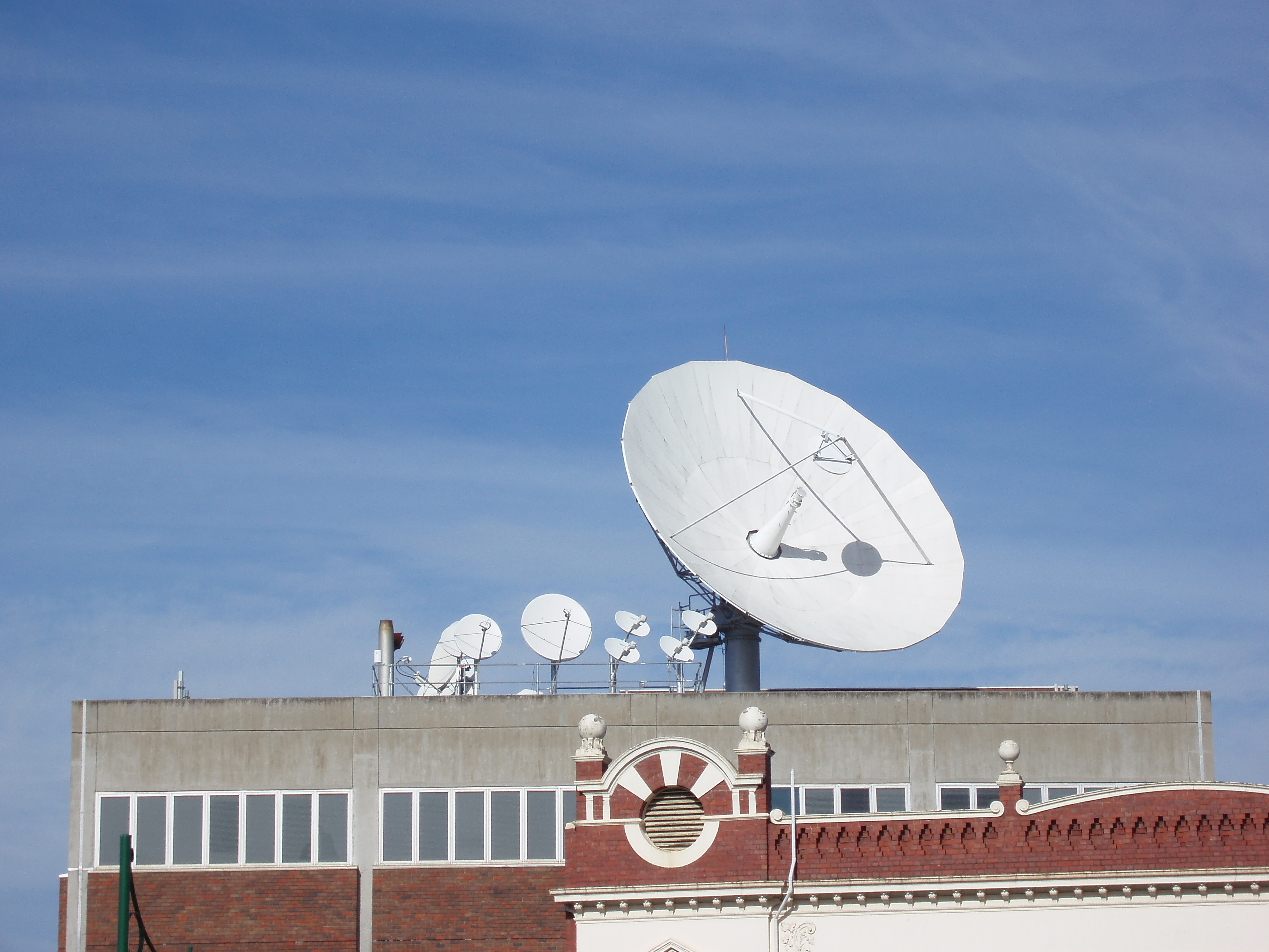 a large satellite dish mounted on a roof top with several other smaller dishes