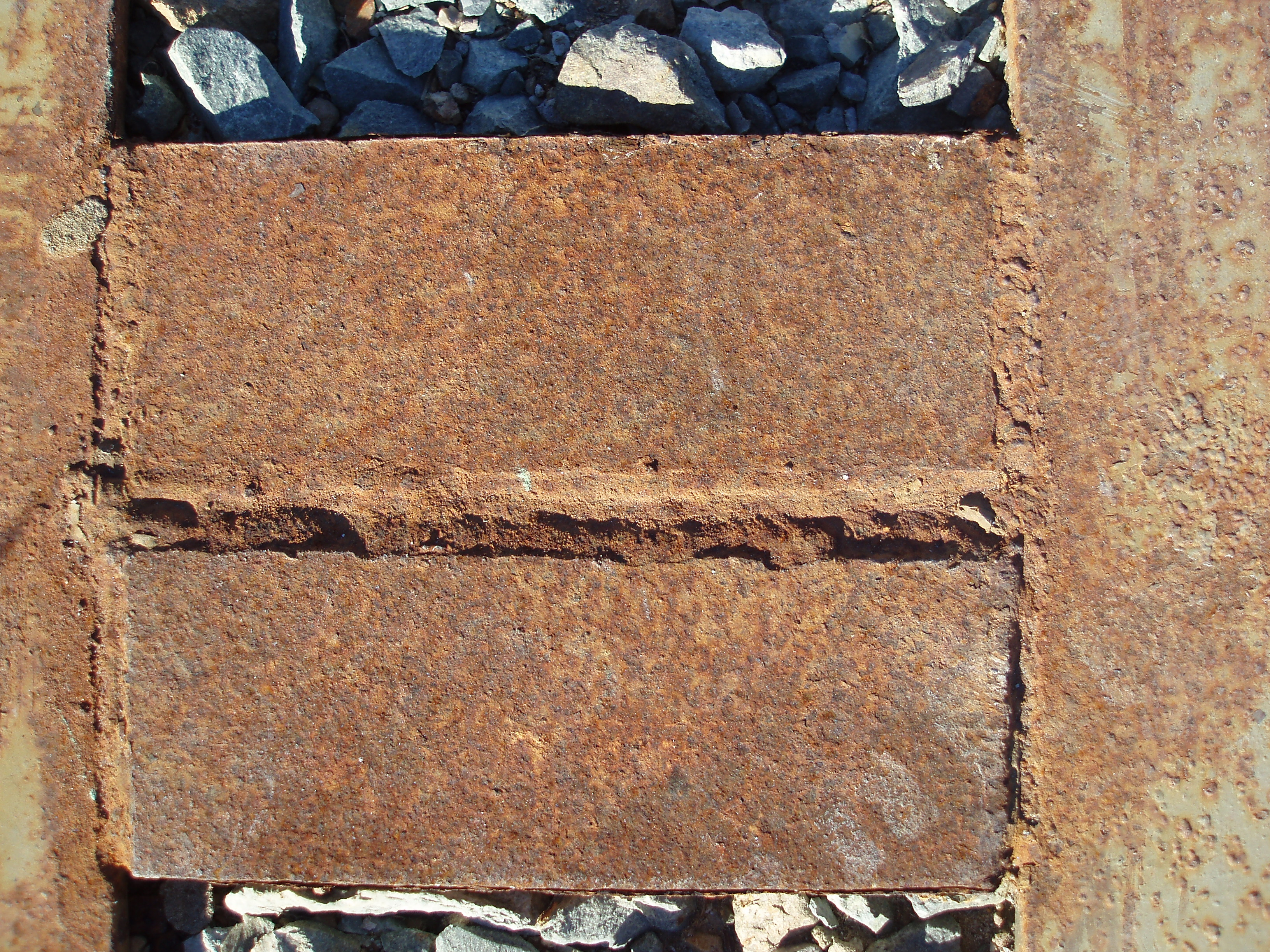 a heavy iron girder pitted with surface rust