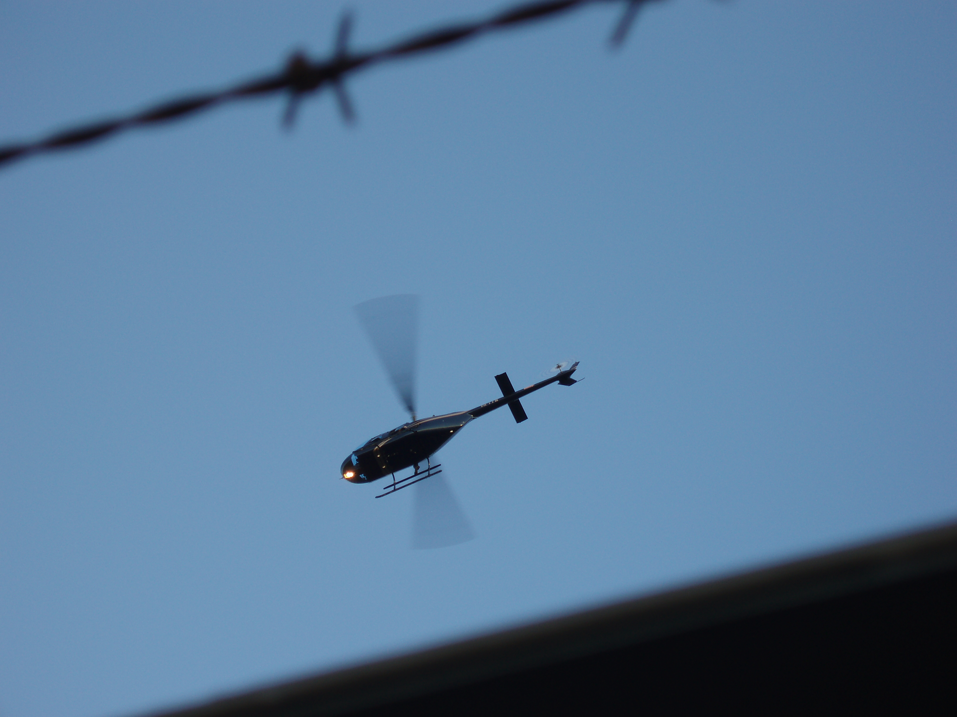 looking up towards a helecopter through a wire fence