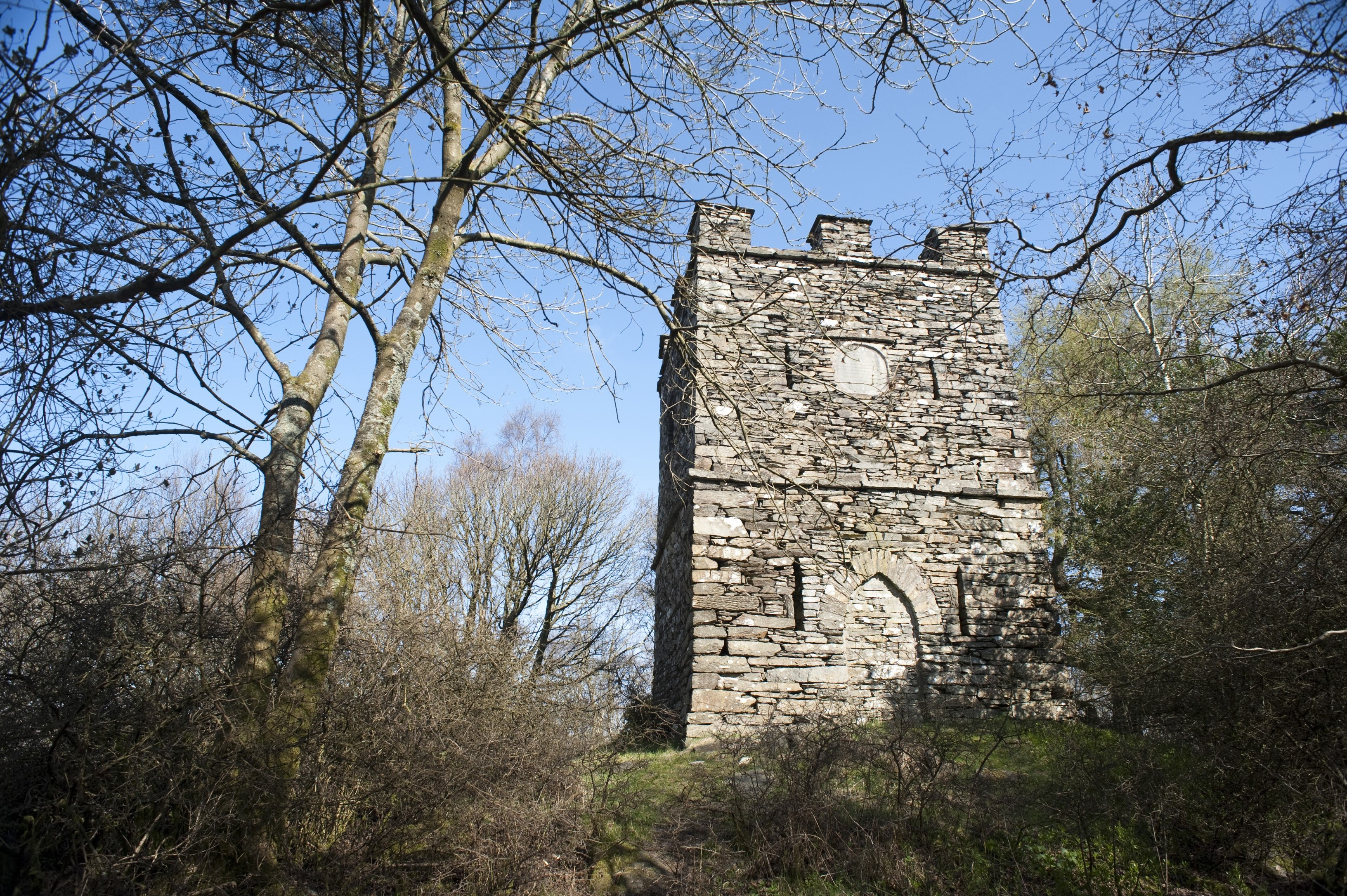 Square stone folly with crenellations in the forest, a building built for whimsical reasons or as a conversation piece during Victorian times