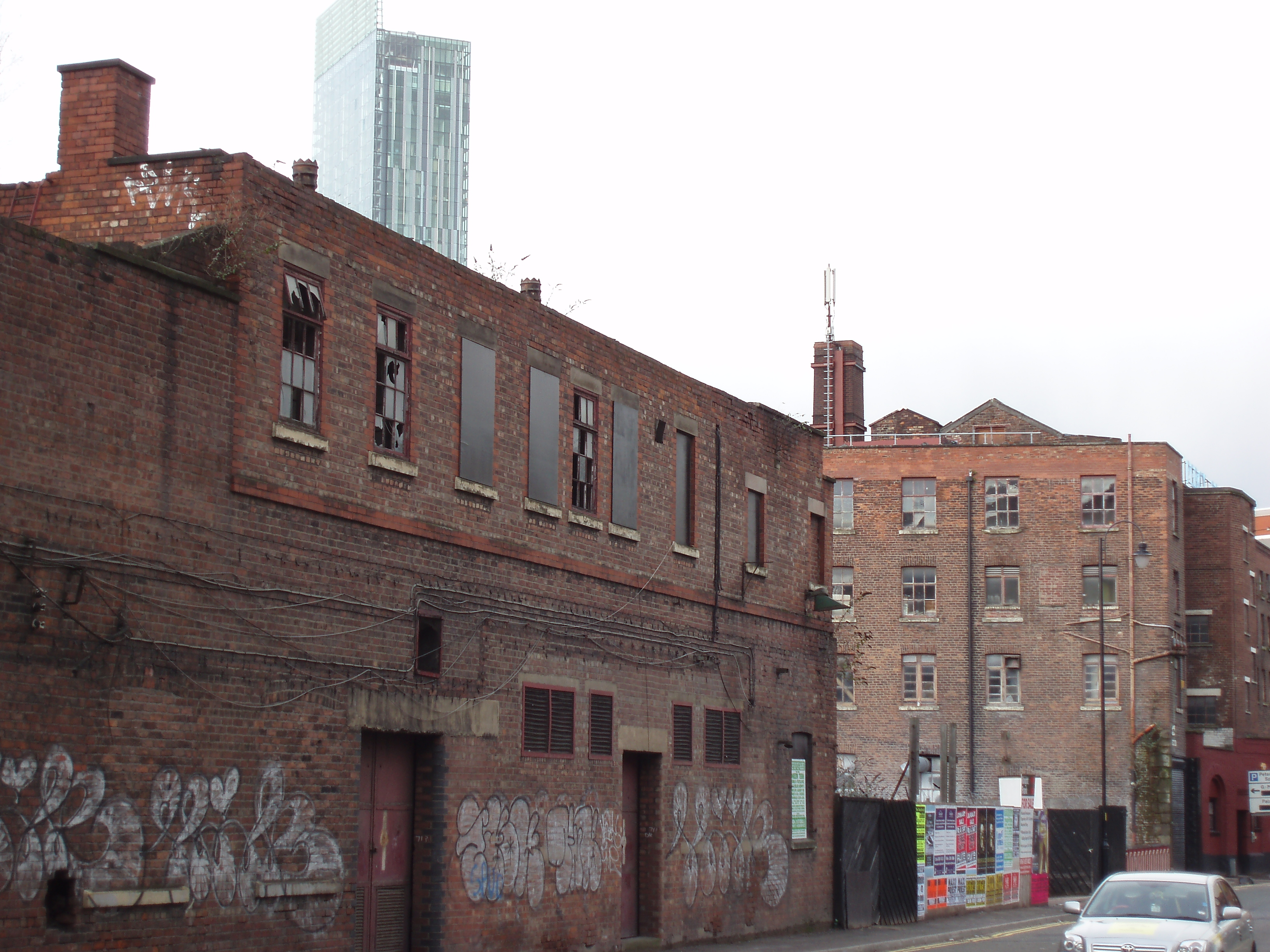 Manchester rundown warehouse with modern hotel and appartments in the background