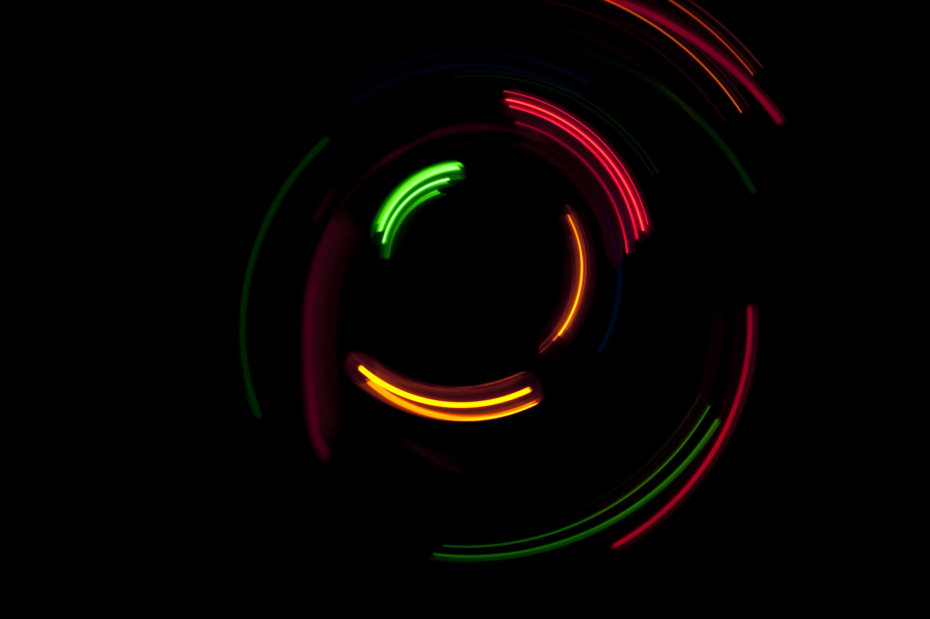 curved arcs of red, yellow, and green light formed around a central point