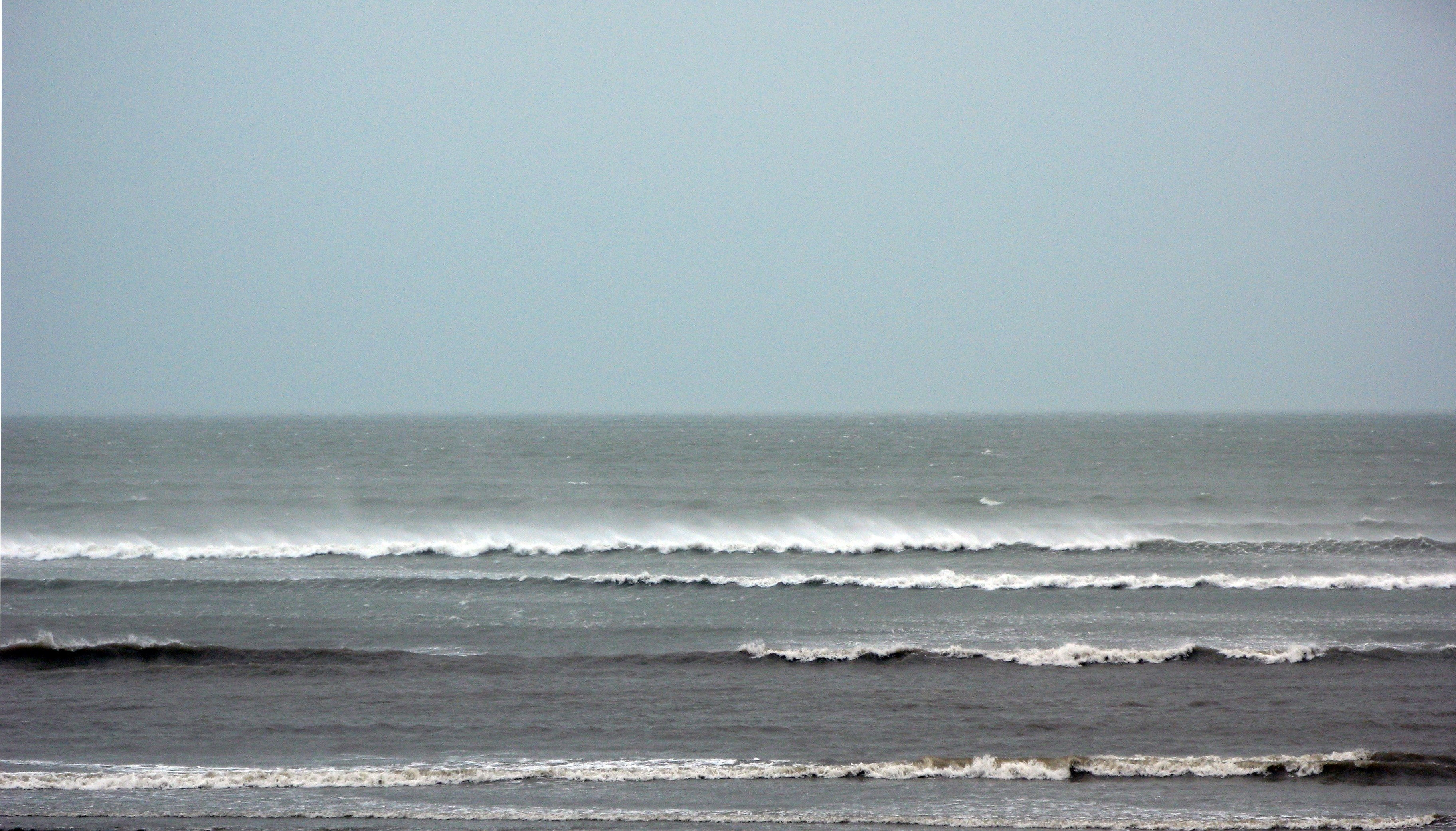 a view out to sea during a cyclone, strong wind blows the tops of breaking waves