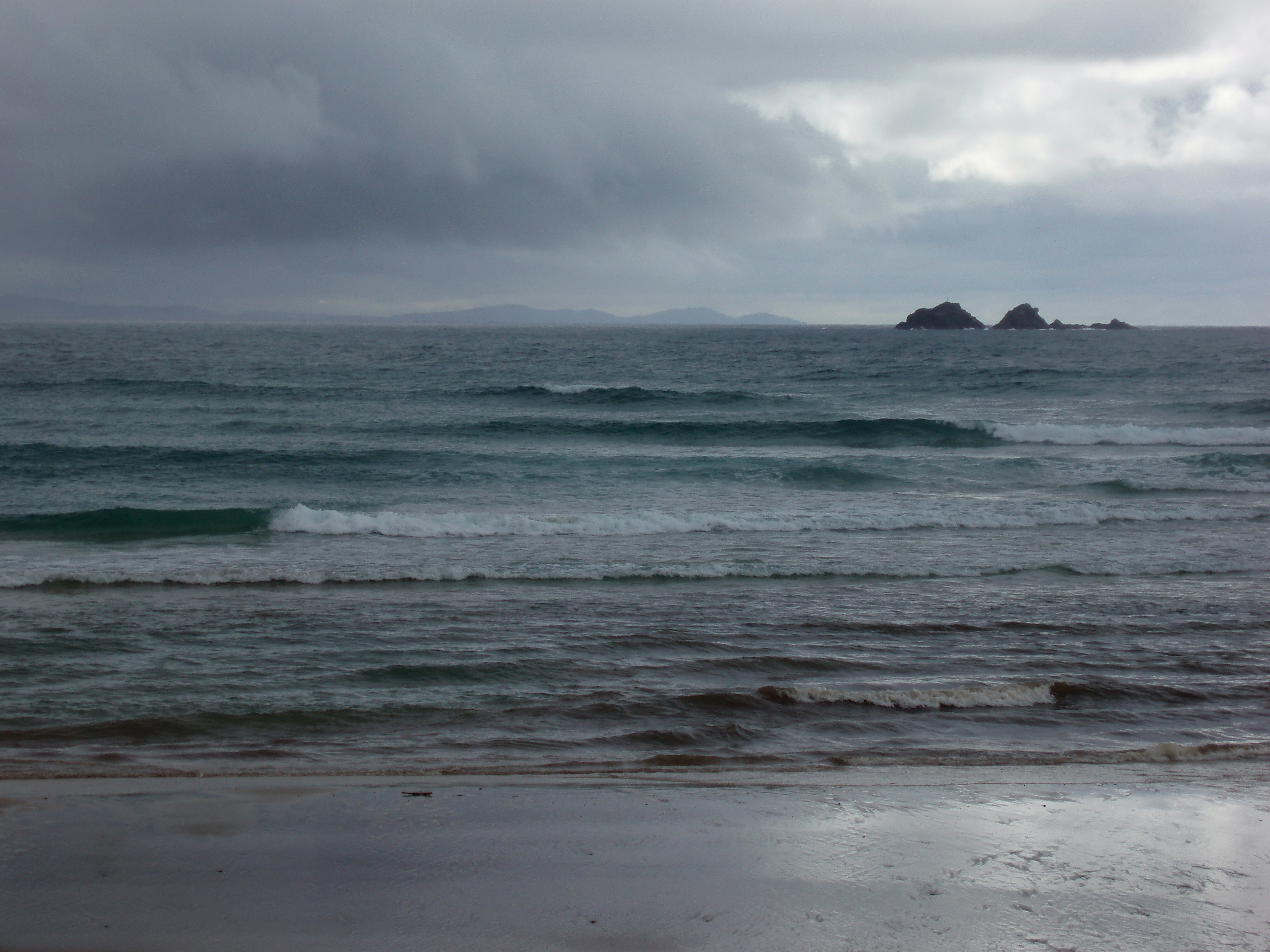 waves breaking on the beach on a grey stormy day
