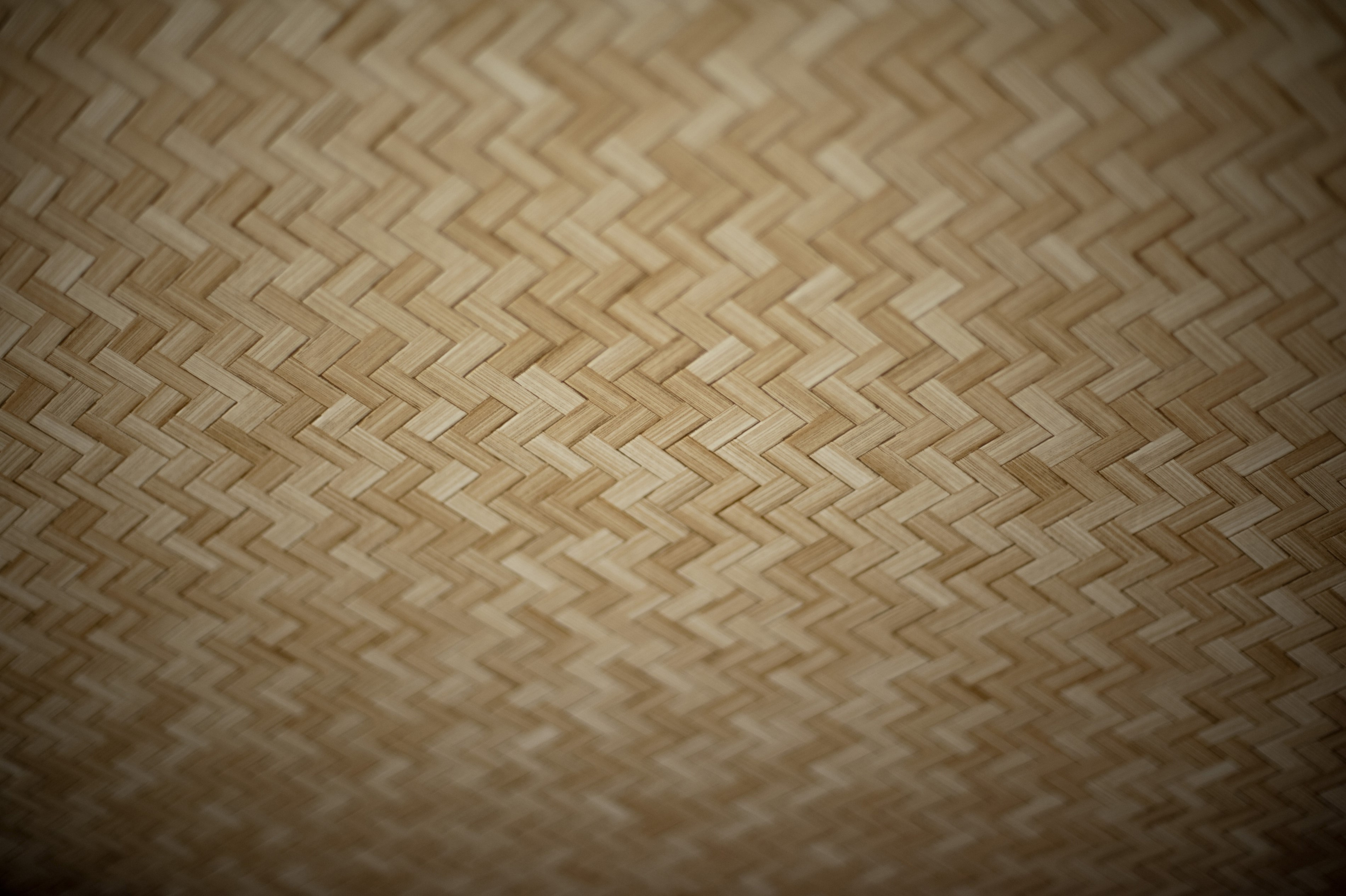 Background texture and repeat zigzag pattern of a woven bamboo ceiling with corner vignetting