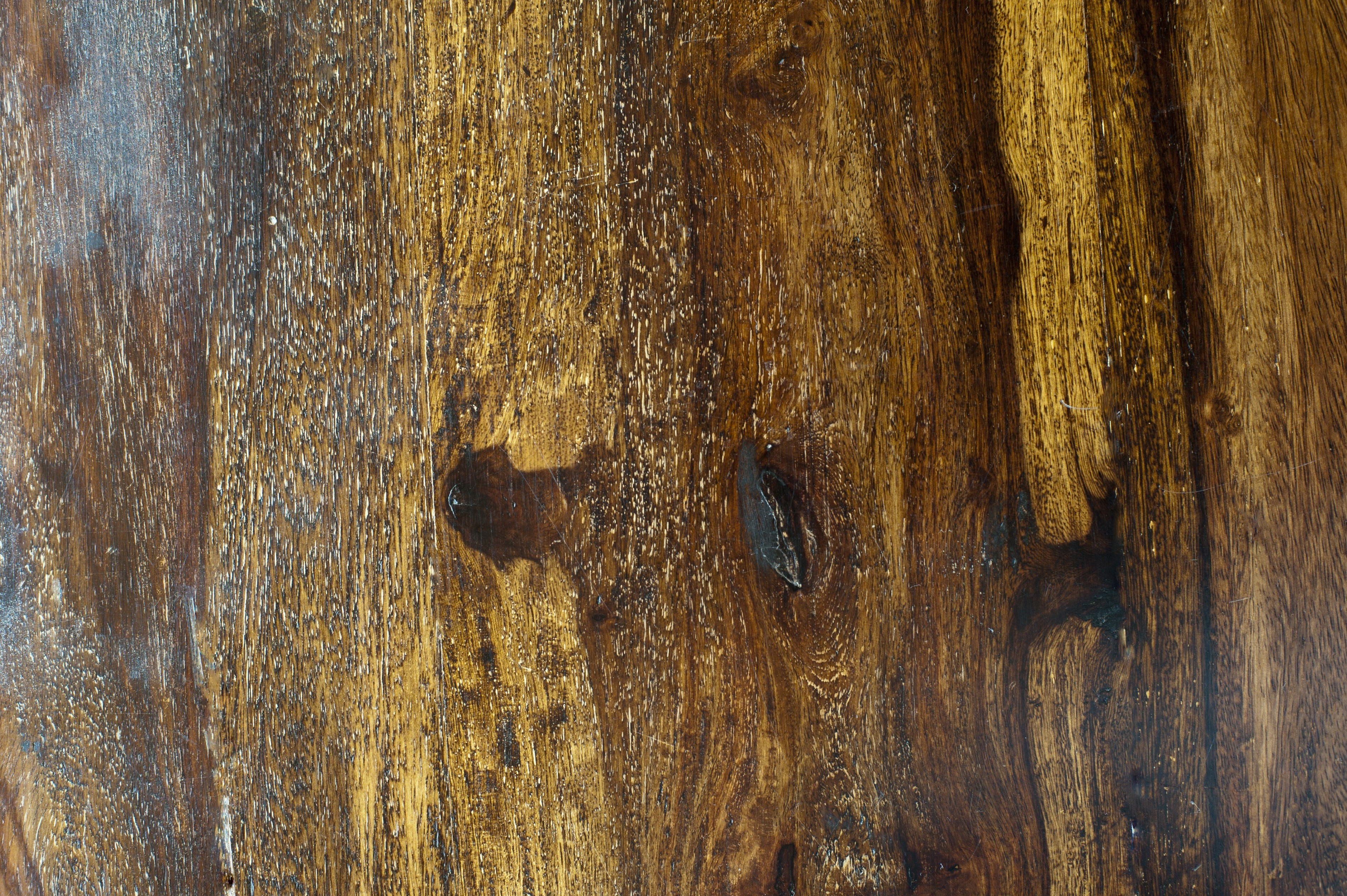 macro closeup image of a dark polished wood surface showing details of the wood grain