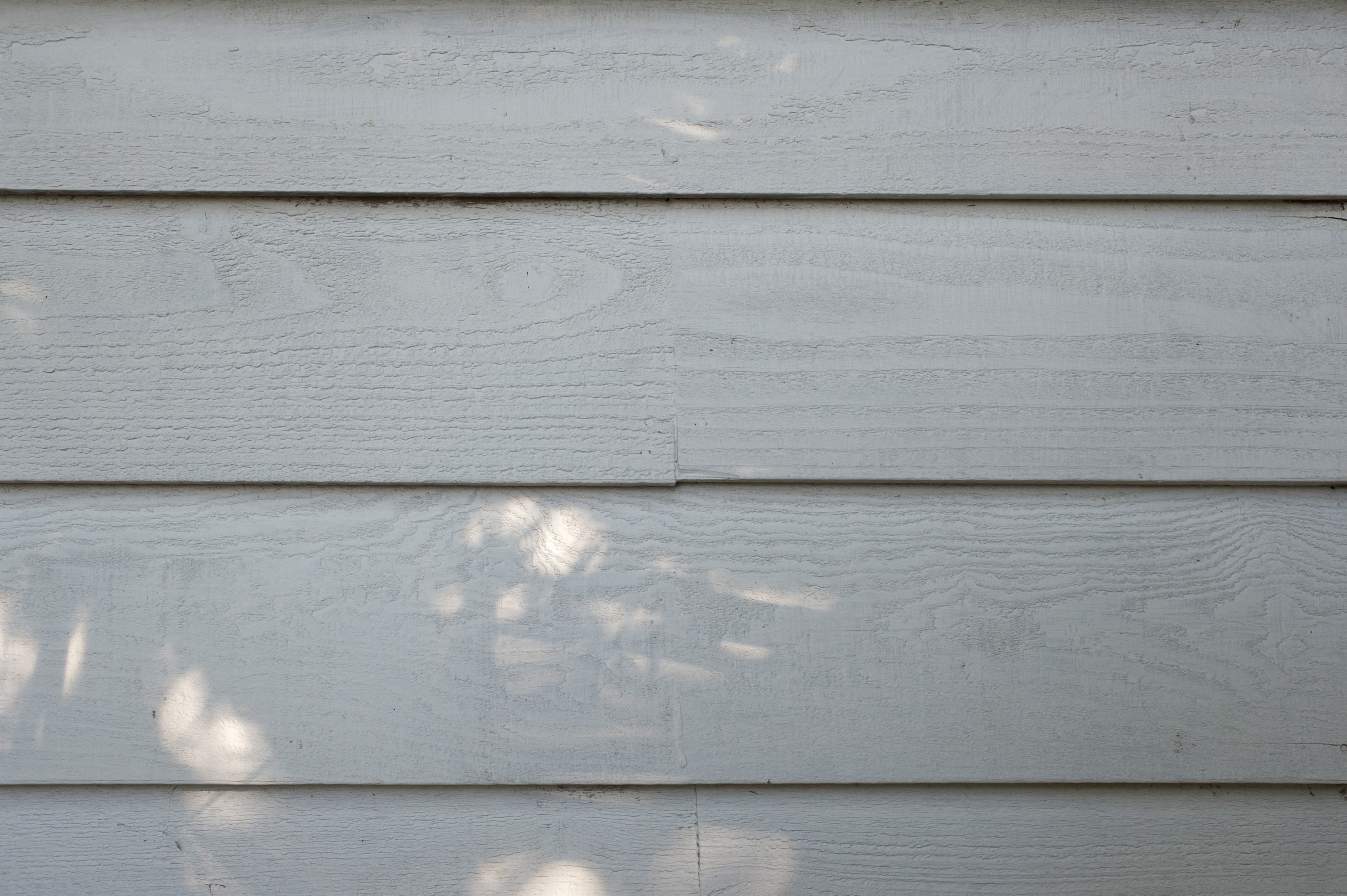 Old painted weatherboards or clapboards used as a cladding and construction material on the exterior of a building