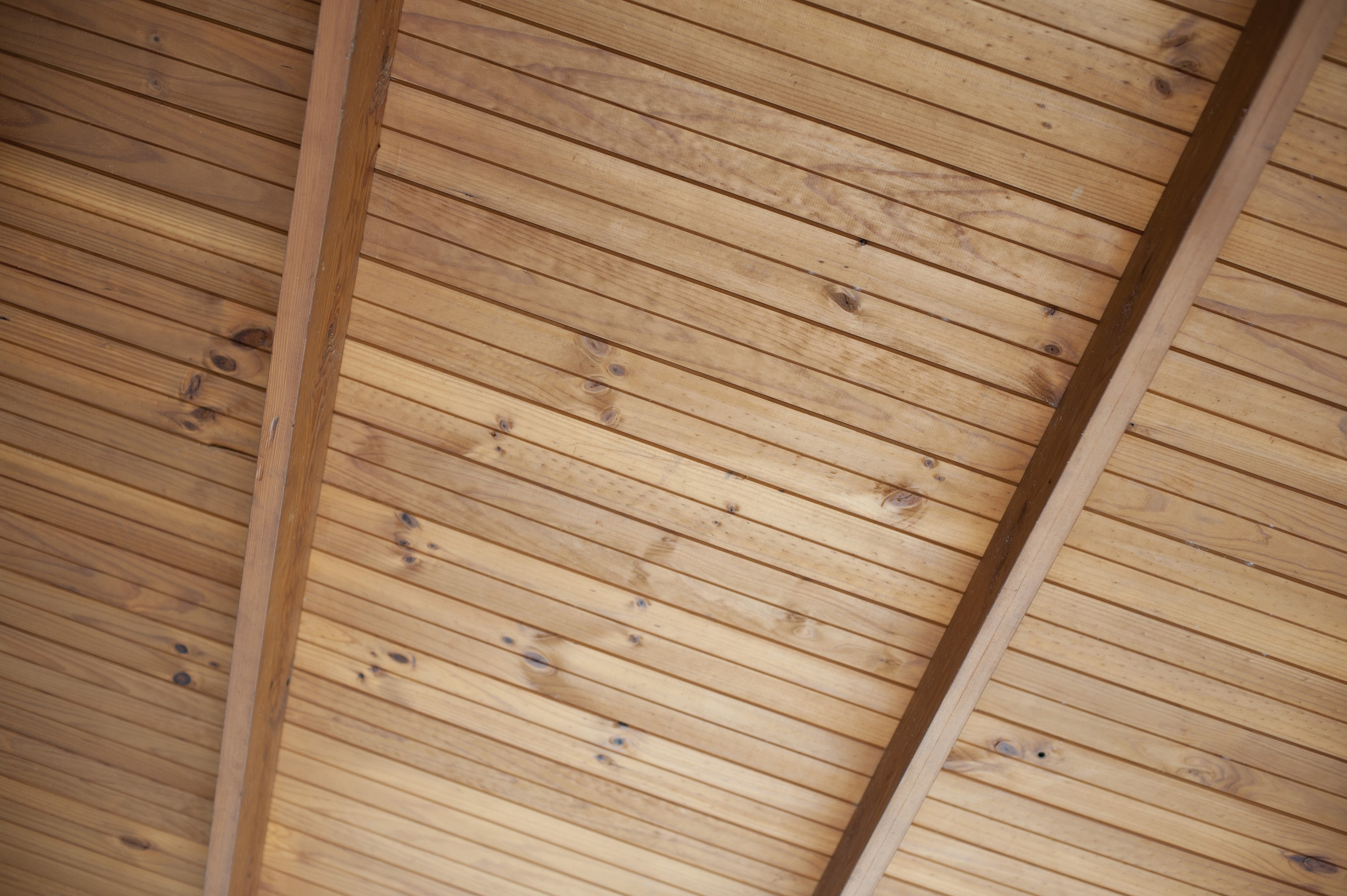 View from underneath of a wooden ceiling made from natural unpolished wooden planks on cross beams