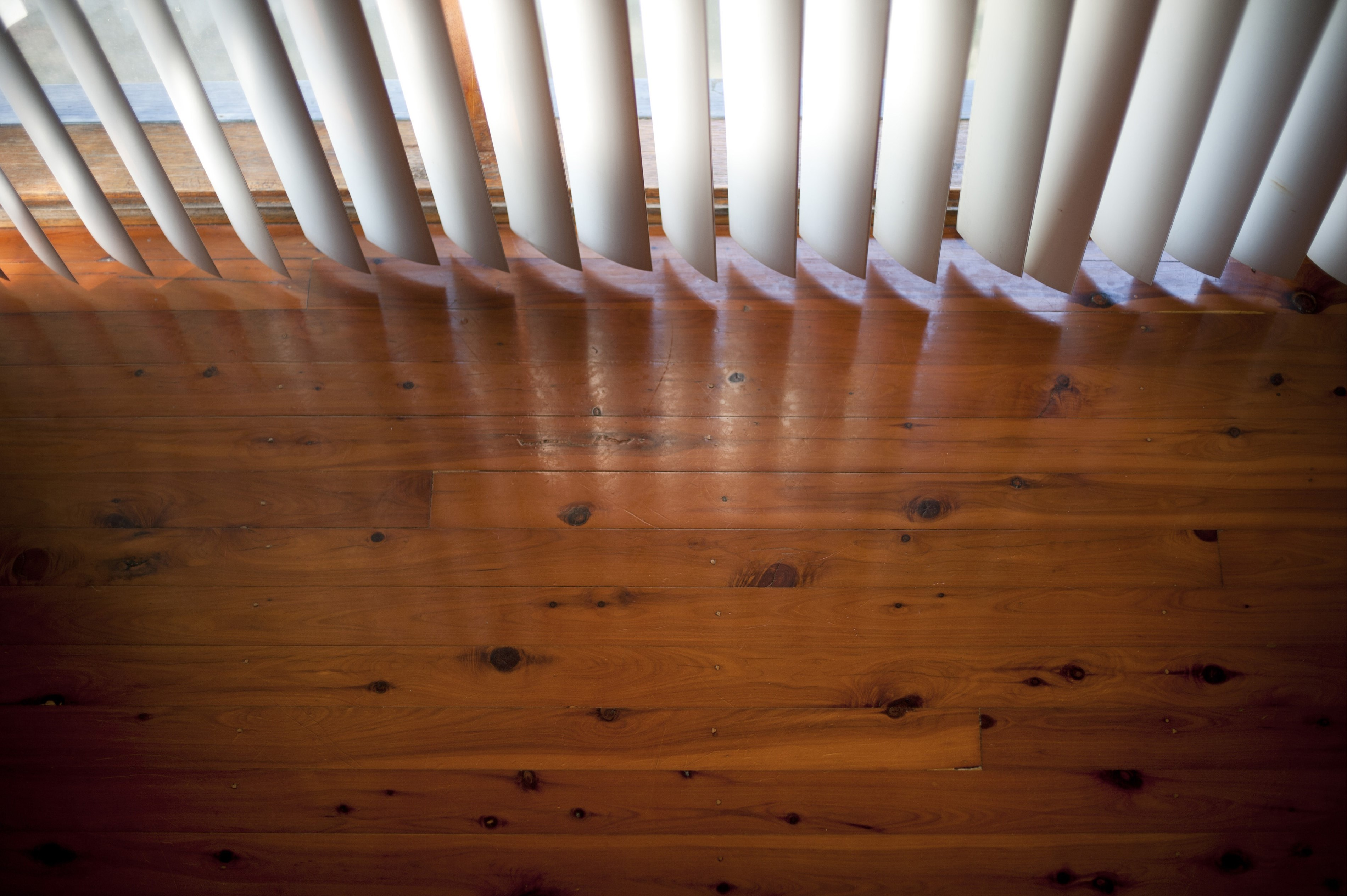 Stained and sealed wooden hardwood interior flooring, high angle view with a vertical blind