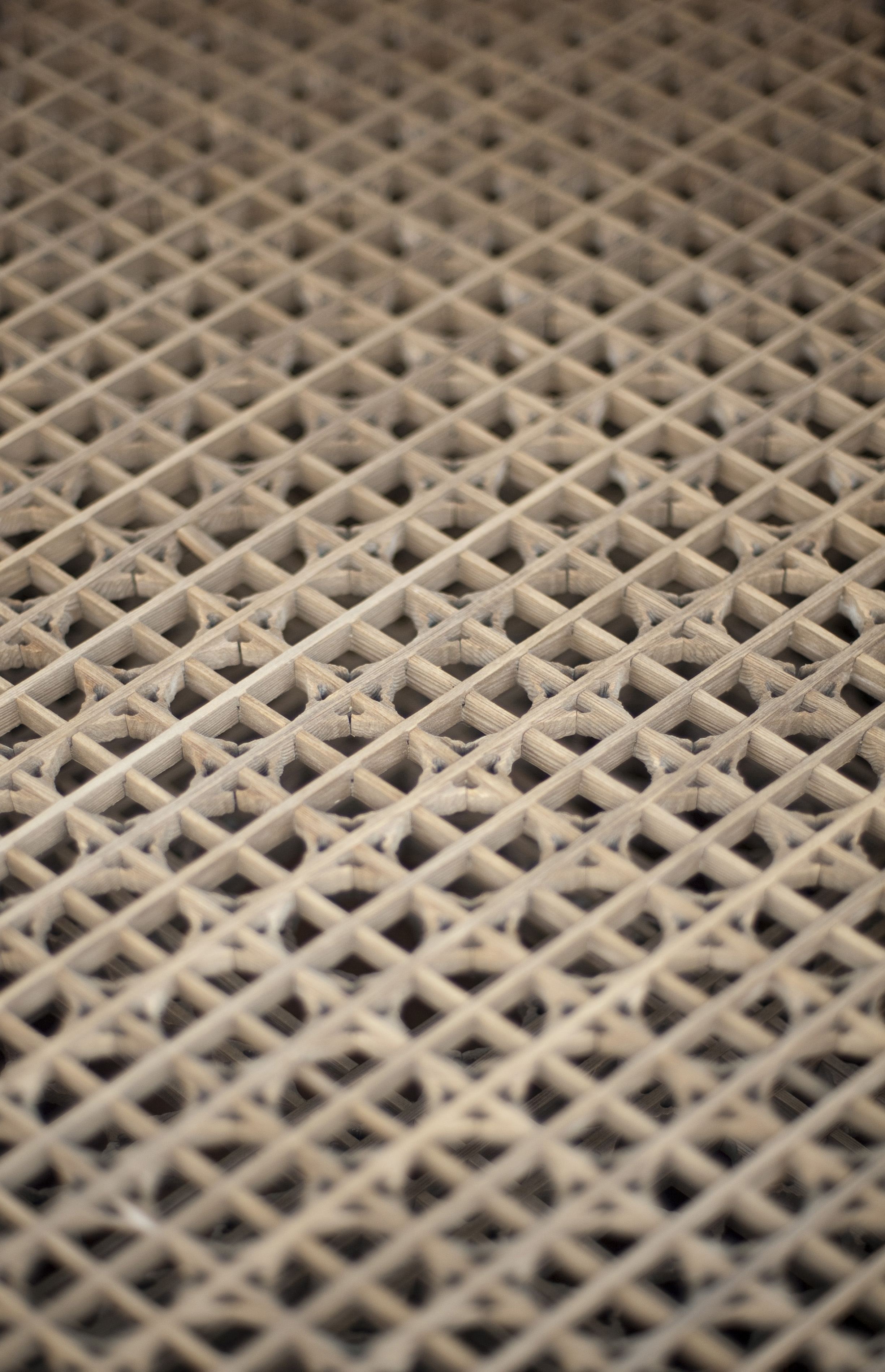 Wooden lattice with a diamond pattern viewed from a high angle with shallow dof on a receding perspective